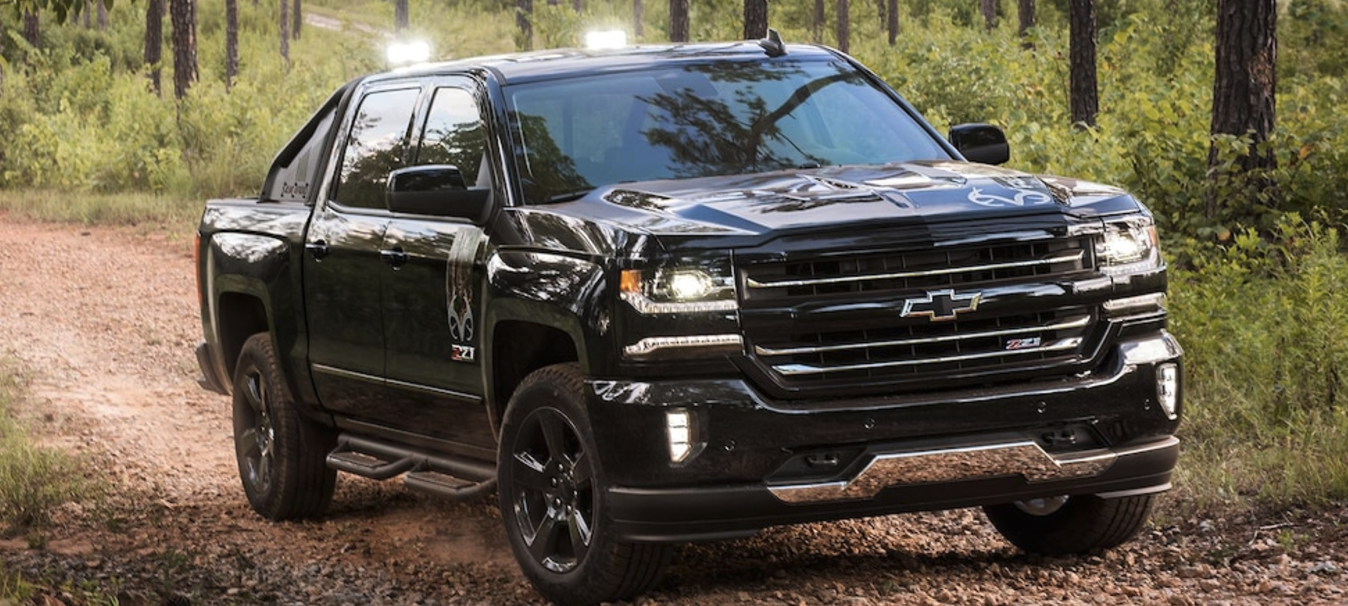 A Black Chevy Silverado Realtree Driving Through The Woods